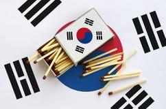 Le drapeau de la Corée du Sud est montré sur une boîte d'allumettes ouverte, de laquelle plusieurs matchs tombent et des mensonge image libre de droits