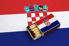Le drapeau de la Croatie est montré dans une boîte d'allumettes ouverte, qui est remplie de matchs et se trouve sur un grand drap photos libres de droits