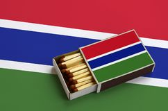 Le drapeau de la Gambie est montré dans une boîte d'allumettes ouverte, qui est remplie de matchs et se trouve sur un grand drape photos stock