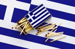 Le drapeau de la Grèce est montré sur une boîte d'allumettes ouverte, de laquelle plusieurs matchs tombent et des mensonges sur u photo libre de droits