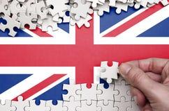 Le drapeau de la Grande-Bretagne est dépeint sur une table sur laquelle la main humaine plie un puzzle de couleur blanche photos libres de droits