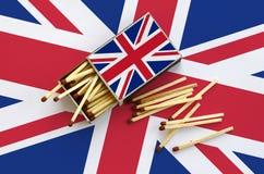Le drapeau de la Grande-Bretagne est montré sur une boîte d'allumettes ouverte, de laquelle plusieurs matchs tombent et des menso image libre de droits