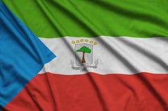 Le drapeau de la Guinée équatoriale est dépeint sur un tissu de tissu de sports avec beaucoup de plis Bannière d'équipe de sport images stock