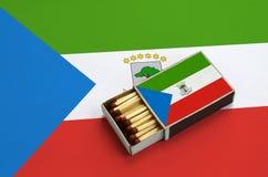 Le drapeau de la Guinée équatoriale est montré dans une boîte d'allumettes ouverte, qui est remplie de matchs et se trouve sur un image stock