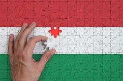 Le drapeau de la Hongrie est dépeint sur un puzzle, que la main du ` s d'homme accomplit pour plier image stock