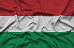 Le drapeau de la Hongrie est dépeint sur un tissu de tissu de sports avec beaucoup de plis Bannière d'équipe de sport image stock