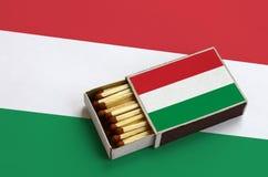 Le drapeau de la Hongrie est montré dans une boîte d'allumettes ouverte, qui est remplie de matchs et se trouve sur un grand drap images stock