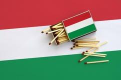 Le drapeau de la Hongrie est montré sur une boîte d'allumettes ouverte, de laquelle plusieurs matchs tombent et des mensonges sur photo libre de droits