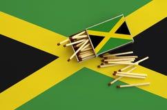 Le drapeau de la Jamaïque est montré sur une boîte d'allumettes ouverte, de laquelle plusieurs matchs tombent et des mensonges su photographie stock libre de droits