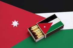 Le drapeau de la Jordanie est montré dans une boîte d'allumettes ouverte, qui est remplie de matchs et se trouve sur un grand dra photographie stock