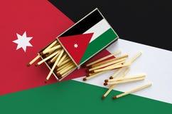 Le drapeau de la Jordanie est montré sur une boîte d'allumettes ouverte, de laquelle plusieurs matchs tombent et des mensonges su images libres de droits