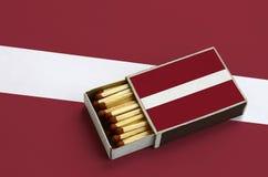 Le drapeau de la Lettonie est montré dans une boîte d'allumettes ouverte, qui est remplie de matchs et se trouve sur un grand dra images stock