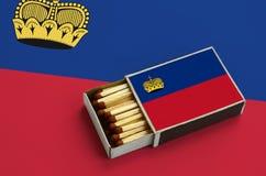 Le drapeau de la Liechtenstein est montré dans une boîte d'allumettes ouverte, qui est remplie de matchs et se trouve sur un gran image stock