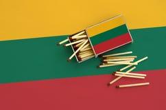 Le drapeau de la Lithuanie est montré sur une boîte d'allumettes ouverte, de laquelle plusieurs matchs tombent et des mensonges s photographie stock libre de droits