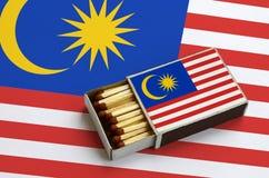 Le drapeau de la Malaisie est montré dans une boîte d'allumettes ouverte, qui est remplie de matchs et se trouve sur un grand dra images stock