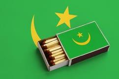 Le drapeau de la Mauritanie est montré dans une boîte d'allumettes ouverte, qui est remplie de matchs et se trouve sur un grand d image libre de droits