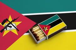 Le drapeau de la Mozambique est montré dans une boîte d'allumettes ouverte, qui est remplie de matchs et se trouve sur un grand d images libres de droits
