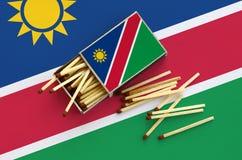Le drapeau de la Namibie est montré sur une boîte d'allumettes ouverte, de laquelle plusieurs matchs tombent et des mensonges sur image libre de droits