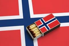 Le drapeau de la Norvège est montré dans une boîte d'allumettes ouverte, qui est remplie de matchs et se trouve sur un grand drap photo libre de droits