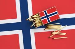 Le drapeau de la Norvège est montré sur une boîte d'allumettes ouverte, de laquelle plusieurs matchs tombent et des mensonges sur photographie stock libre de droits