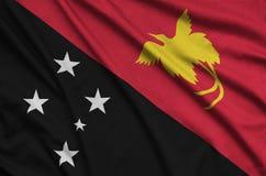 Le drapeau de la Papouasie-Nouvelle-Guinée est dépeint sur un tissu de tissu de sports avec beaucoup de plis Bannière d'équipe de photos stock