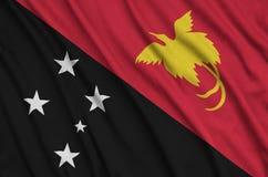 Le drapeau de la Papouasie-Nouvelle-Guinée est dépeint sur un tissu de tissu de sports avec beaucoup de plis Bannière d'équipe de images stock