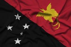 Le drapeau de la Papouasie-Nouvelle-Guinée est dépeint sur un tissu de tissu de sports avec beaucoup de plis Bannière d'équipe de images libres de droits