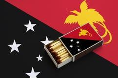 Le drapeau de la Papouasie-Nouvelle-Guinée est montré dans une boîte d'allumettes ouverte, qui est remplie de matchs et se trouve illustration stock