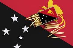 Le drapeau de la Papouasie-Nouvelle-Guinée est montré sur une boîte d'allumettes ouverte, de laquelle plusieurs matchs tombent et photos libres de droits