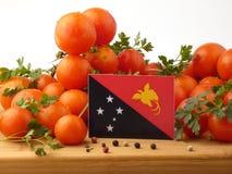Le drapeau de la Papouasie-Nouvelle-Guinée sur un panneau en bois avec des tomates a isolé o photo libre de droits