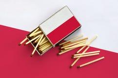 Le drapeau de la Pologne est montré sur une boîte d'allumettes ouverte, de laquelle plusieurs matchs tombent et des mensonges sur photographie stock libre de droits