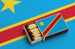 Le drapeau de la République démocratique du Congo est montré dans une boîte d'allumettes ouverte, qui est remplie de matchs et se photographie stock