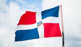 Le drapeau de la République Dominicaine ondule au-dessus du ciel nuageux Images libres de droits