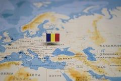 Le drapeau de la Roumanie dans la carte du monde photos stock