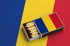 Le drapeau de la Roumanie est montré dans une boîte d'allumettes ouverte, qui est remplie de matchs et se trouve sur un grand dra photos libres de droits