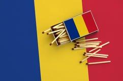 Le drapeau de la Roumanie est montré sur une boîte d'allumettes ouverte, de laquelle plusieurs matchs tombent et des mensonges su photo stock