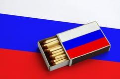 Le drapeau de la Russie est montré dans une boîte d'allumettes ouverte, qui est remplie de matchs et se trouve sur un grand drape image stock