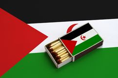 Le drapeau de la Sahara occidental est montré dans une boîte d'allumettes ouverte, qui est remplie de matchs et se trouve sur un  photo libre de droits