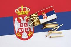 Le drapeau de la Serbie est montré sur une boîte d'allumettes ouverte, de laquelle plusieurs matchs tombent et des mensonges sur  photos stock
