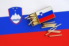 Le drapeau de la Slovénie est montré sur une boîte d'allumettes ouverte, de laquelle plusieurs matchs tombent et des mensonges su image stock