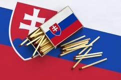 Le drapeau de la Slovaquie est montré sur une boîte d'allumettes ouverte, de laquelle plusieurs matchs tombent et des mensonges s images stock