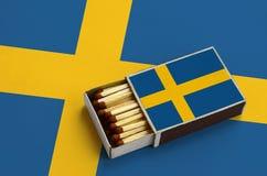 Le drapeau de la Suède est montré dans une boîte d'allumettes ouverte, qui est remplie de matchs et se trouve sur un grand drapea images libres de droits