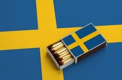 Le drapeau de la Suède est montré dans une boîte d'allumettes ouverte, qui est remplie de matchs et se trouve sur un grand drapea image libre de droits