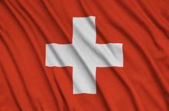 Le drapeau de la Suisse est dépeint sur un tissu de tissu de sports avec beaucoup de plis Bannière d'équipe de sport images libres de droits