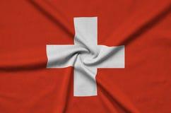 Le drapeau de la Suisse est dépeint sur un tissu de tissu de sports avec beaucoup de plis Bannière d'équipe de sport photographie stock libre de droits
