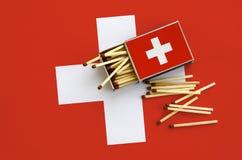 Le drapeau de la Suisse est montré sur une boîte d'allumettes ouverte, de laquelle plusieurs matchs tombent et des mensonges sur  photos libres de droits