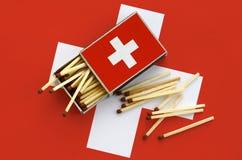 Le drapeau de la Suisse est montré sur une boîte d'allumettes ouverte, de laquelle plusieurs matchs tombent et des mensonges sur  photo libre de droits