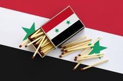 Le drapeau de la Syrie est montré sur une boîte d'allumettes ouverte, de laquelle plusieurs matchs tombent et des mensonges sur u photo stock
