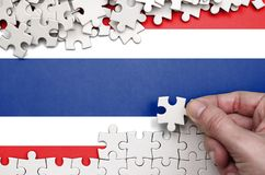 Le drapeau de la Thaïlande est dépeint sur une table sur laquelle la main humaine plie un puzzle de couleur blanche photos stock