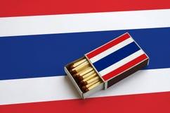 Le drapeau de la Thaïlande est montré dans une boîte d'allumettes ouverte, qui est remplie de matchs et se trouve sur un grand dr photographie stock